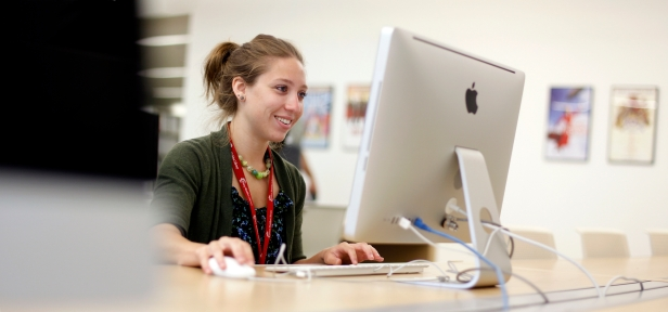 A female student smiles while working at a computer in the Library's media lab