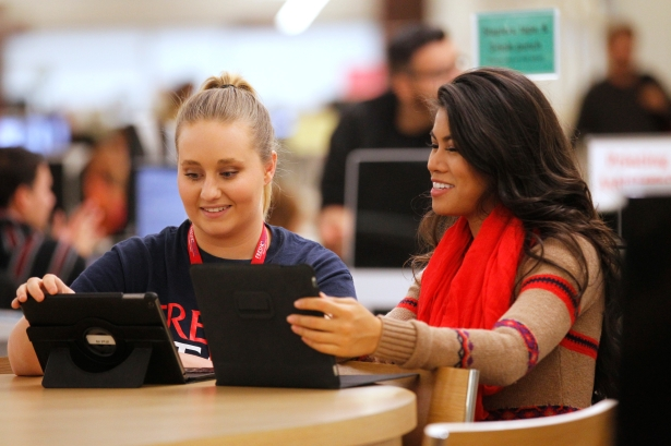 Two students sit at a desk in the new library and look at tablets