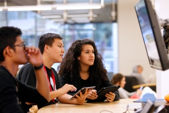 Students gather at a table with tablets in hand, while viewing a screen above them
