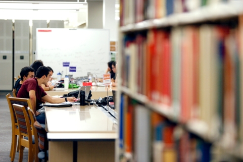 Students sit at tables surround by bookshelves in the library with books and laptops