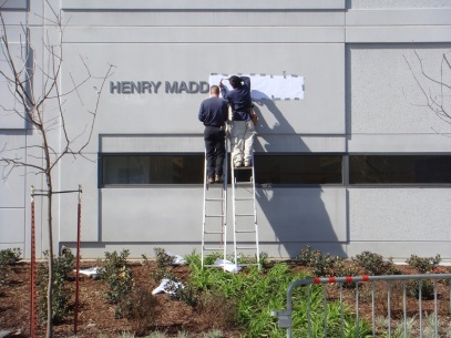 Two workers stand on ladders to install a new sign on the Library's exterior wall