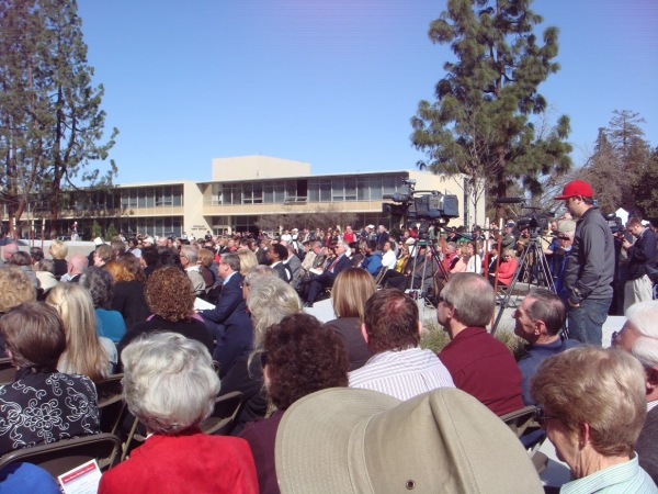 A crowd gathers for the grand reopening of the Library while TV cameras capture the event.