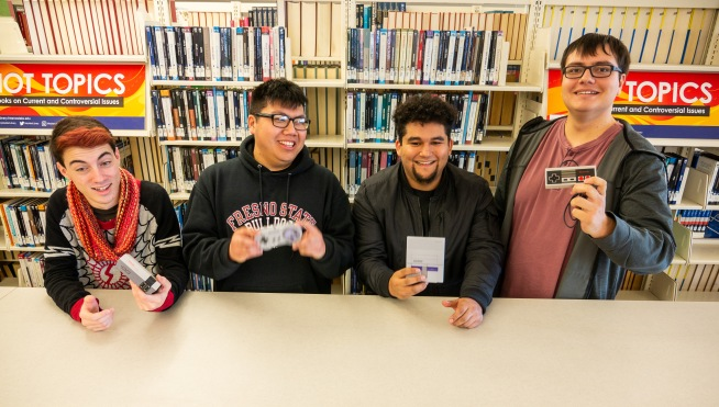 Four students pose in the Library with vintage video game equipment