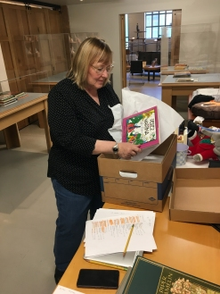 Jennifer Crow unpacks books for display at the exhibition