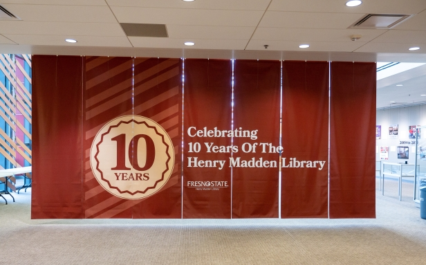 "A banner with the words ""Celebrating 10 Years of The Henry Madden Library"" in the Leon S. Peters Eclipse Gallery."