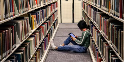 Student sits in between two large bookshelves in the library